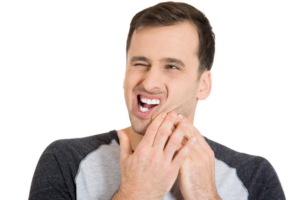 man holding jaw from pain during dental emergency