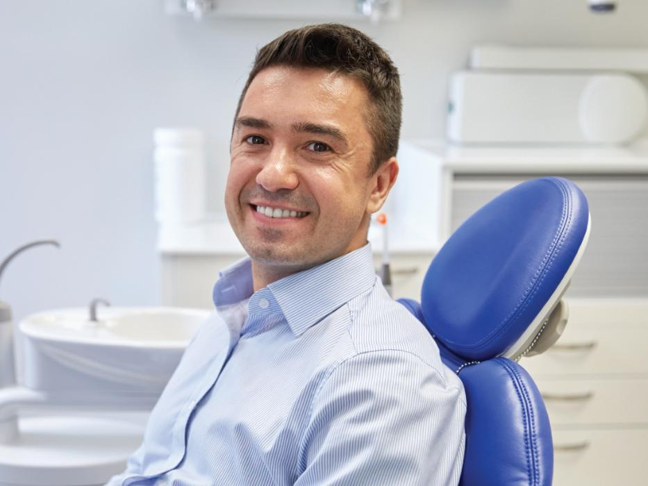 man sitting in dental chair after getting dentures | dentist brentwood tn