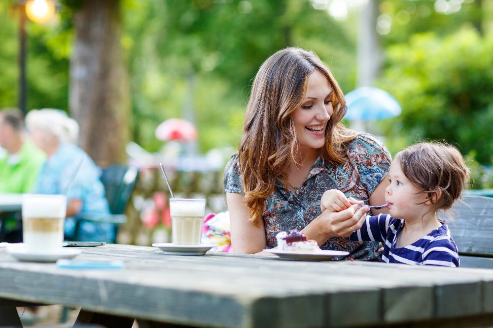 mom sitting with baby at picnic table | dentist brentwood tn